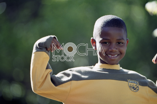 Smiling young boy flexing his muscles.