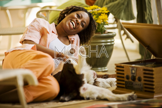 Woman lying on the floor with her dog while listening to music on a record player.