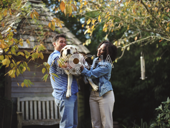 Happy mid-adult couple patting their dog in the back yard of their home.