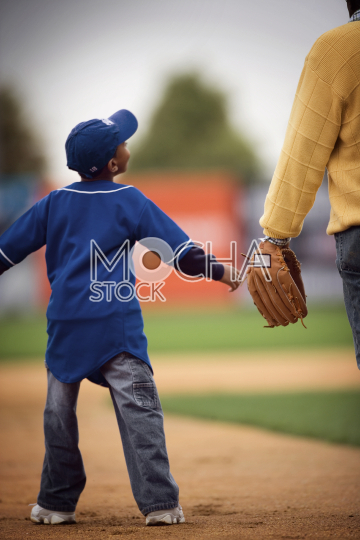 Young baseball player walking with father
