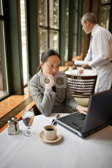 Businesswoman working on her laptop in a cafe with a male waiter setting the table behind her.