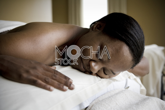 Content mid adult woman lying on a massage table with her eyes closed.