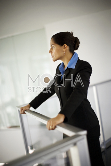 Mid-adult business woman leaning on a banister inside an office building