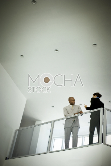 A mid-adult businessman leaning on a banister inside an office building speaking with a female colleague