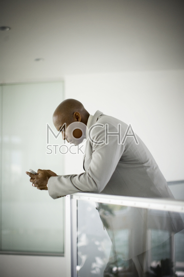 Mid-adult businessman leaning on a banister whilst texting on his cellphone in an office building