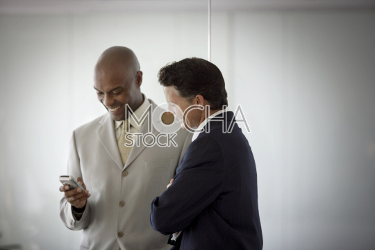 Two smiling mid-adult businessman looking a cellphone