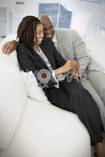 Happy corporate couple sitting on a couch