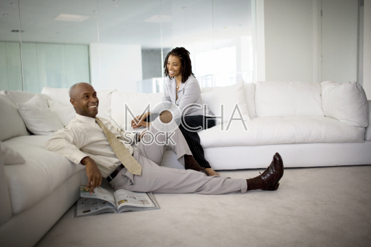 Smiling mid-adult man sitting on the floor reading a magazine while his wife looks at him from the couch