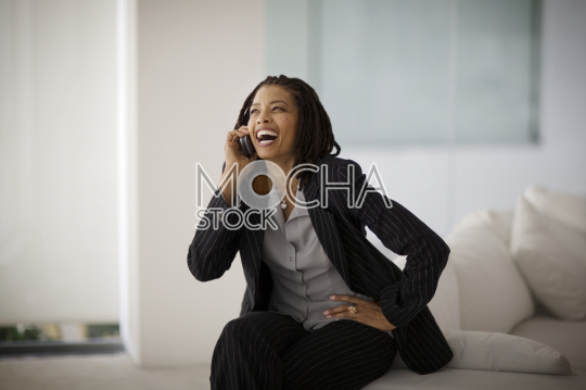 Laughing mid-adult business woman talking on a cellphone while sitting on a couch