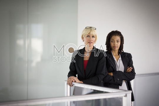 Two confident business women standing in hallway