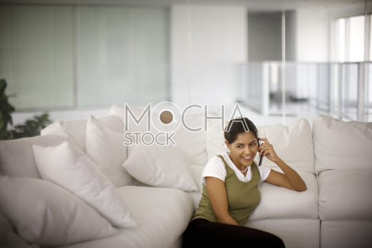 Smiling mid-adult woman talking on a cell phone indoors