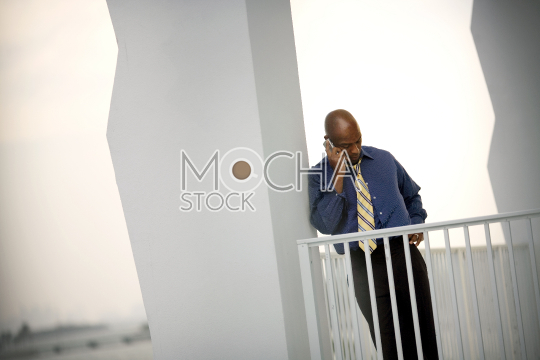 Mid-adult businessman talking on a cell phone while standing on a balcony