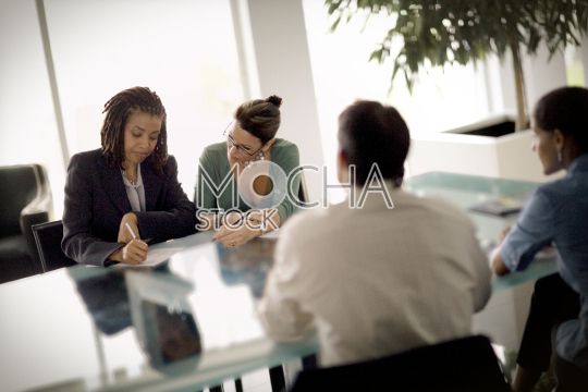 Business colleagues sitting around a table in a boardroom
