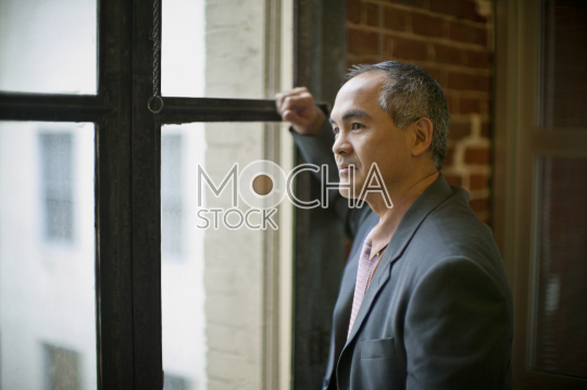 Portrait of businessman looking out of the window in his office