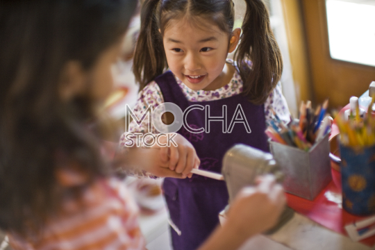 Young girl with her hair in pigtails sharpening a pencil with her friend