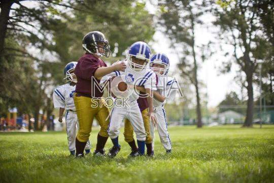 Group of young boys playing American football on a grassy lawn in a park