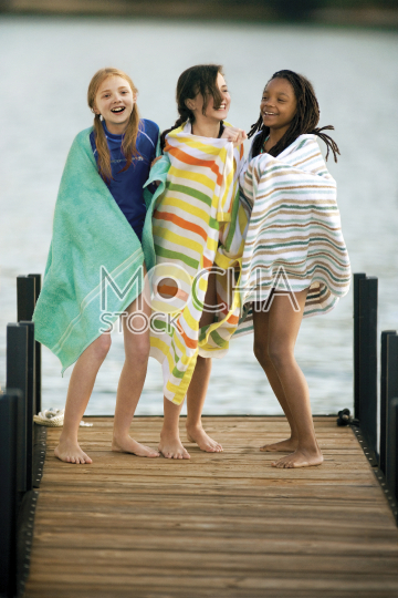 Three laughing girls standing on a wooden jetty wrapped in towels