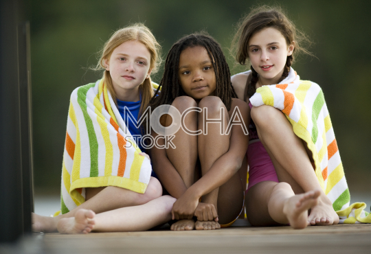 Portrait of three girls sitting on a jetty wearing towels