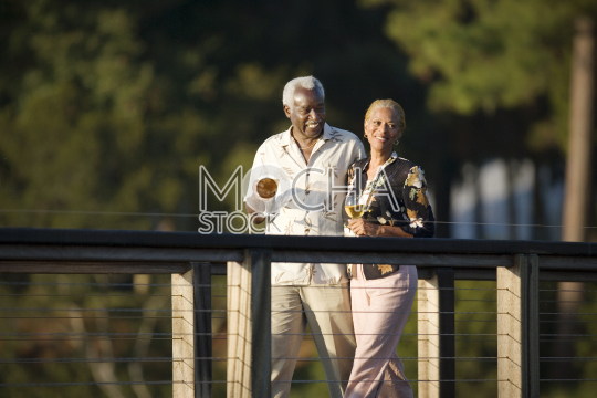Mature adult couple walking along a pier holding glasses of wine