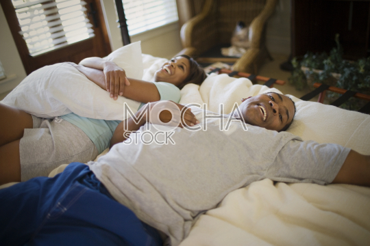 Mid-adult couple lying together on a bed