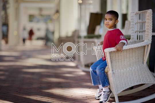 Portrait of a boy sitting on an outdoor rocking chair