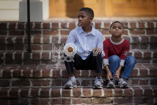 Portrait of a young boy sitting with his older brother on steps and tying his shoe laces