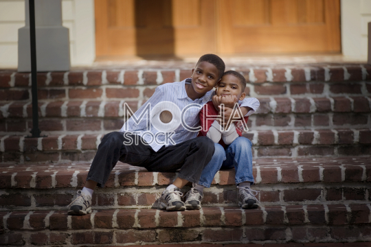 Portrait of a young boy being hugged by his older brother as they sit on steps