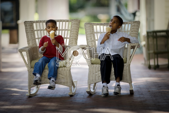 Two boys sitting on outdoor rocking chairs eating ice-cream