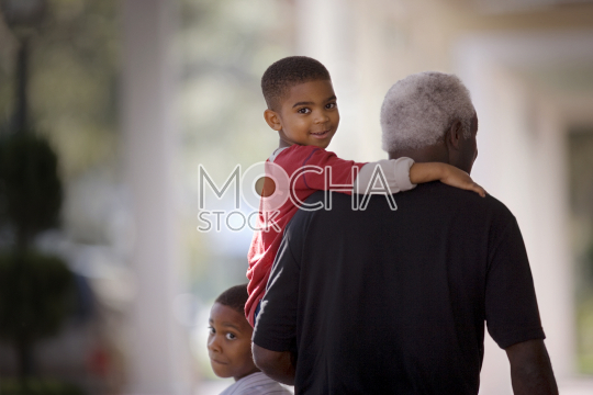Portrait of a young boy being carried by his mature grandfather