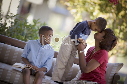Boy sitting with a book as his younger brother rests his head on his mid-adult mother's head