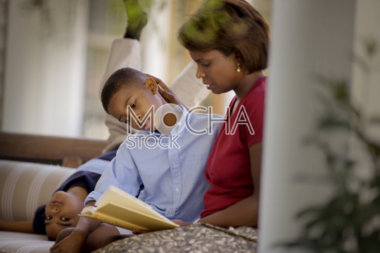 Portrait of a young boy upside down on a couch beside his older brother who is reading with his mid-adult mother