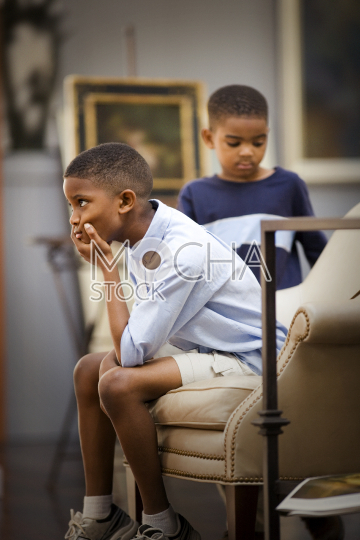 Boy sitting on a chair concentrating as his younger brother stands beside him