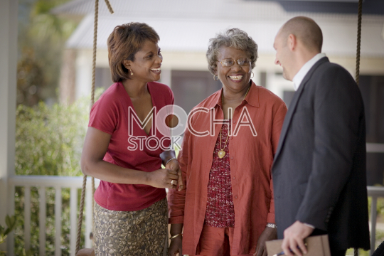 Mid-adult woman and her mature mother on a porch with a male friend
