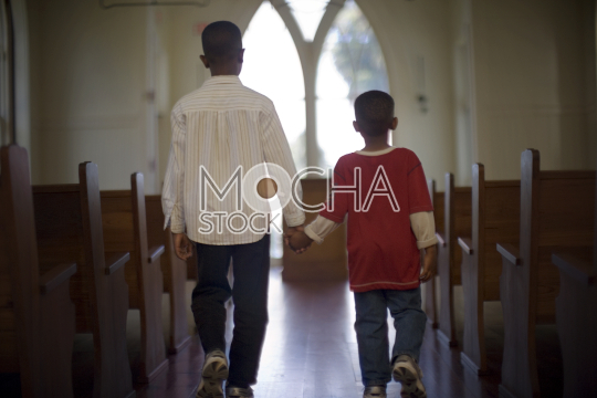 Two boys holding hands while walking down the aisle of a church