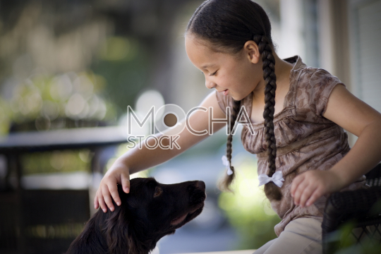 Young girl patting a dog on a porch