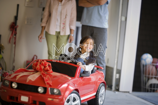 Portrait of a smiling young girl sitting in a small red car given to her as a gift