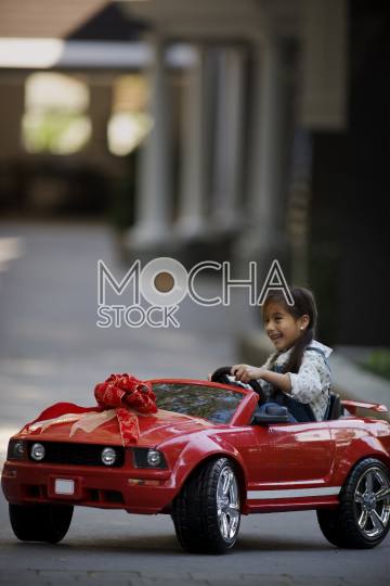 Smiling young girl sitting in a small red car given to her as a gift