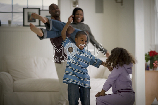 Young brother and sister playing together in their living room with their parents