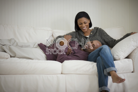 Smiling mid-adult couple on a white sofa together