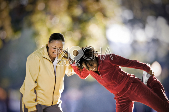 Two mid-adult woman stretching together in a park