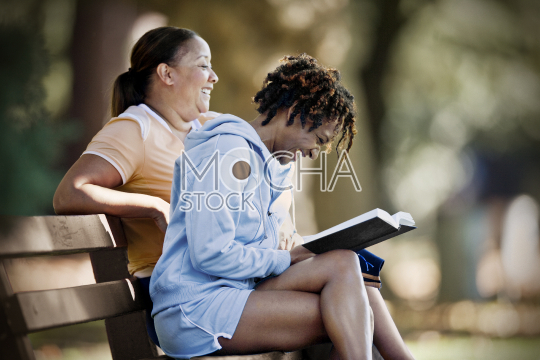 Mid-adult woman sitting on a park bench reading a book with a friend