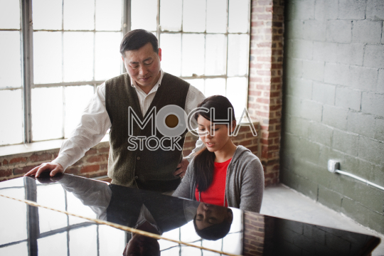 Daughter playing piano while her father stands nearby and watches