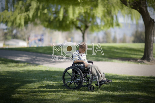 Young boy sitting in a wheelchair at the park
