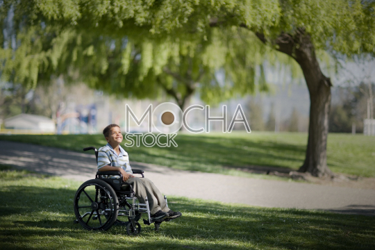 Smiling young boy sitting in a wheelchair at the park